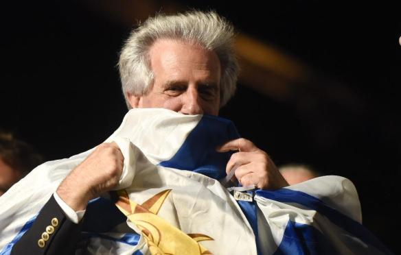 Presidential candidate for the ruling Broad Front party Tabare Vazquez kisses a Uruguya's flag as he celebrates in Montevideo, Uruguay Sunday, Nov. 30, 2014. Exits polls shows that Broad Front coalition candidate and former president Tabare Vazquez has won the presidential elections.(AP Photo/Matilde Campodonico)