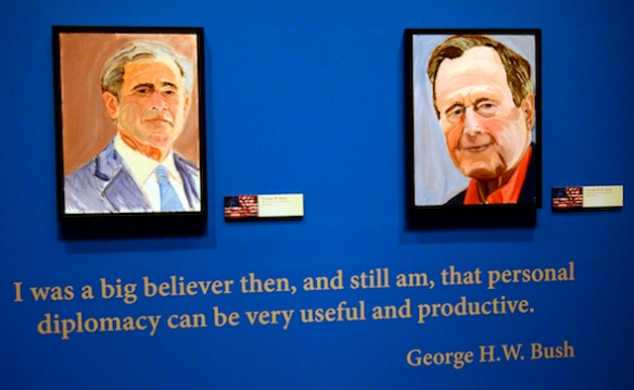 """Portraits of former Presidents Goerge W. Bush, left, and his father George H.W. Bush which are part of the exhibit """"The Art of Leadership: A President's  Diplomacy,"""" are on display at the George W. Bush Presidential Library and Museum in Dallas, Friday, April 4, 2014. The exhibit of world leader portraits painted by George W. Bush opens Saturday and runs through June 3.  (AP Photo/Benny Snyder)"""