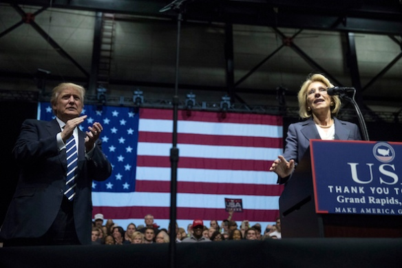 President-elect Donald Trump, left, applauds as his pick for Education Secretary Betsy DeVos, right, speaks during a rally at DeltaPlex Arena, Friday, Dec. 9, 2016, in Grand Rapids, Mich. (AP Photo/Andrew Harnik)
